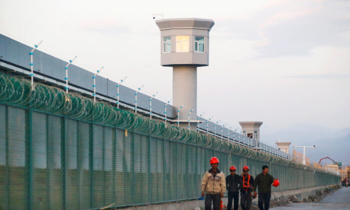 Workers walk by the perimeter fence of a labor camp in Xinjiang on Sept. 4, 2018. (Thomas Peter/Reuters)
