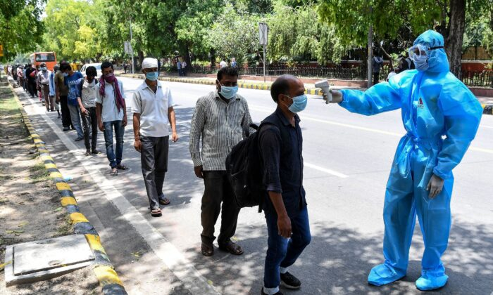 A volunteer wearing a protective suit checks the body temperature of homeless people standing in queue to get free lunch packets on the roadside after the goverment eased a nationwide lockdown as a preventive measure against the COVID-19 coronavirus, in New Delhi on May 30, 2020. (Prakash Singh/AFP via Getty Images)