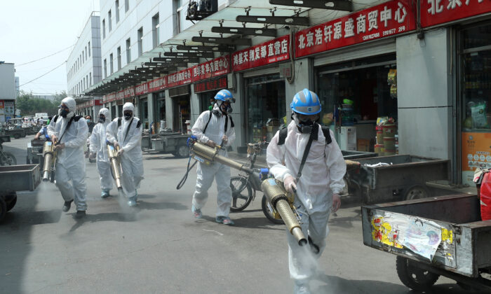 Volunteers from Blue Sky Rescue team in protective suits disinfect the Yuegezhuang wholesale market, following new cases of coronavirus disease (COVID-19) infections in Beijing, China, on June 16, 2020. (China Daily via Reuters)