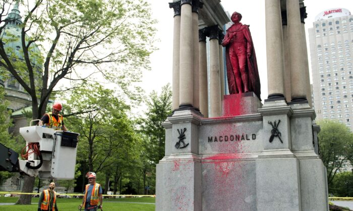 City workers prepare to clean the statue of Sir John A. Macdonald in downtown Montreal on Aug. 17, 2018, after it was vandalized the previous night. (The Canadian Press/Graham Hughes)