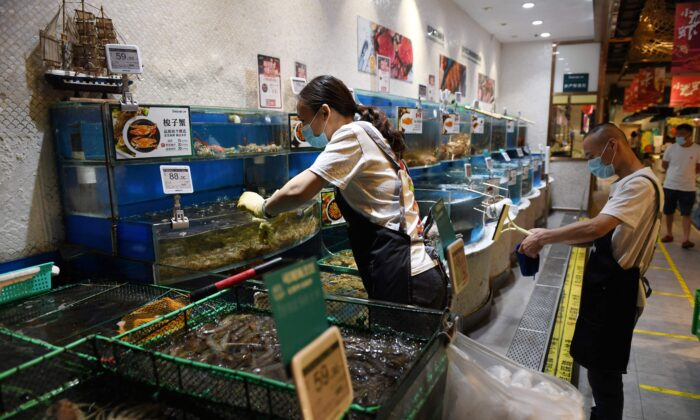 A worker is seen in the seafood section of a supermarket in Beijing, China, on June 17, 2020. (Greg Baker/AFP via Getty Images)