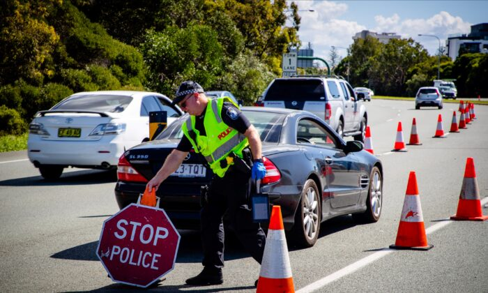 A Queensland police officer moves a stop sign at a vehicle checkpoint on the Pacific Highway on the Queensland - New South Wales border, in Brisbane on April 15, 2020. (Patrick Hamilton/AFP via Getty Images)