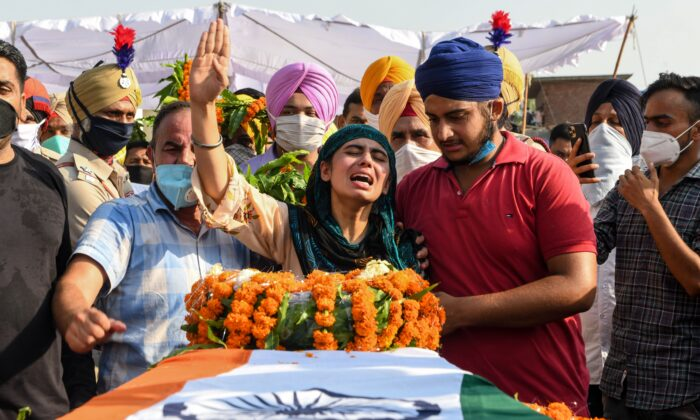 Sandeep Kaur (C) and her brother Prabhjot Singh (2R) react after laying the wreaths of flowers on the coffin of their father and soldier Satnam Singh who was killed in a recent clash with Chinese forces in the Galwan valley area, during the cremation ceremony at Bhojraj village near Gurdaspur on June 18, 2020. (Narinder Nanu/AFP/Getty Images)