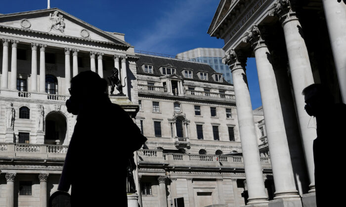 People wearing masks walk past the Bank of England, as the spread of the CCP virus continues, in London on March 23, 2020. (Toby Melville/Reuters)