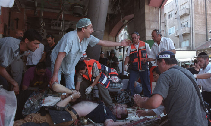 Israeli doctors and medics tend to the injured at the site of a Palestinian suicide bombing in Jerusalem, Israel, on Aug. 9, 2001. At least 18 people, including six children, were killed and more than 80 other people were injured in the blast at a Sbarro pizzeria. (Getty Images)