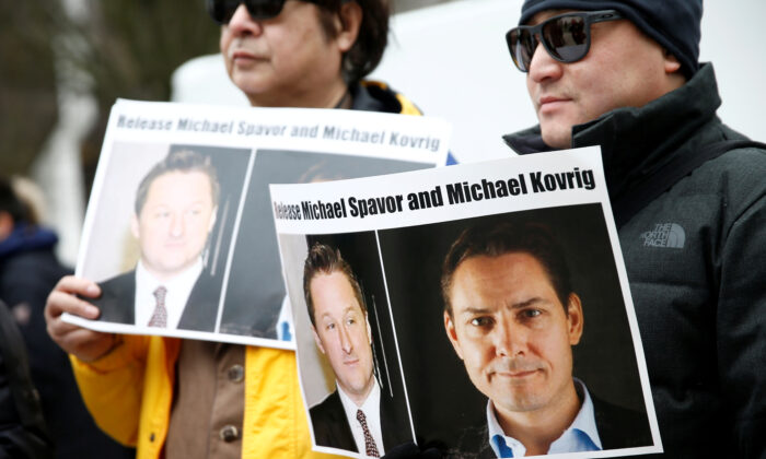 People hold signs calling for China to release Canadian detainees Michael Spavor and Michael Kovrig during an extradition hearing for Huawei Technologies Chief Financial Officer Meng Wanzhou at the B.C. Supreme Court in Vancouver, Canada, on March 6, 2019. (Reuters/Lindsey Wasson)