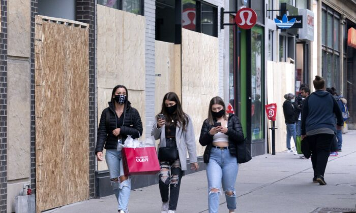 People wear face masks to protect against COVID-19 as they walk along Sainte-Catherine Street in Montreal on June 3, 2020. (Canadian Press/Paul Chiasson)