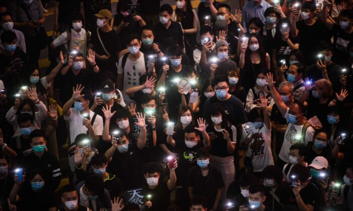 Pro-democracy protesters hold up their mobile phones as they sing during a rally in the Causeway Bay district of Hong Kong on June 12, 2020. (Anthony Wallace/AFP via Getty Images)
