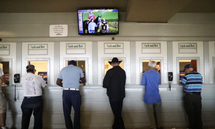 Gamblers stand at betting windows on the final day of the winter/spring horse racing season at Santa Anita Park in Arcadia, Calif., on June 23, 2019. (Mario Tama/Getty Images)