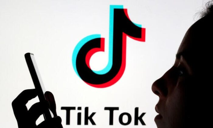 A person holds a smartphone as Tik Tok logo is displayed behind in this picture illustration taken on Nov. 7, 2019. (Dado Ruvic/Reuters)