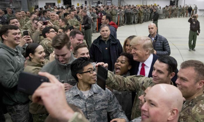 President Donald Trump, center right, and first lady Melania Trump, center left, greet members of the military at Ramstein Air Base, Germany on Dec. 27, 2018. (AP Photo/Andrew Harnik)