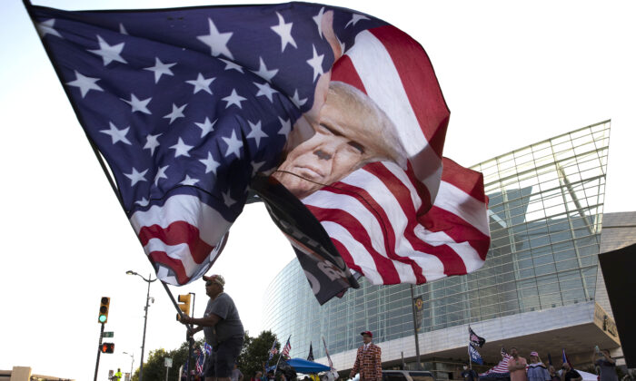 Trump supporter Randall Thom waves a giant Trump flag to passing cars outside the BOK Center in Tulsa, Okla., on June 18, 2020. (Win McNamee/Getty Images)