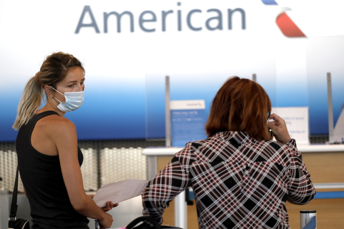 Travelers wait at the American Airlines ticket counter