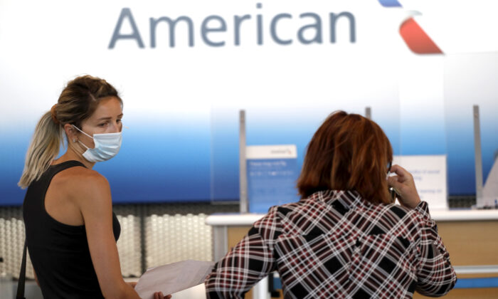 Travelers wear masks as they wait at the American Airlines ticket counter at O'Hare International Airport in Chicago, Ill., on June 16, 2020. (Nam Y. Huh/AP Photo)