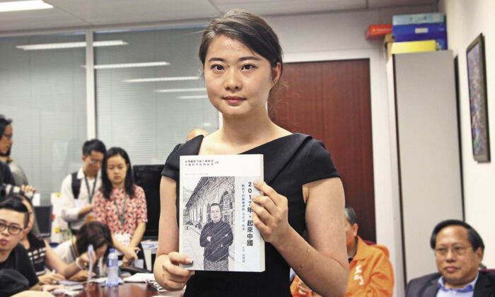 Grace Geng, Gao Zisheng's daughter, holds a copy of Gao's new book at the book-launch ceremony in Hong Kong on June 16, 2016. (Stone Poon/The Epoch Times)
