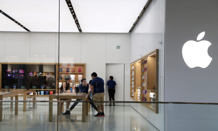 Apple employees work inside a closed Apple store in Miami on March 14 2020. (AP Photo/Lynne Sladky, File)