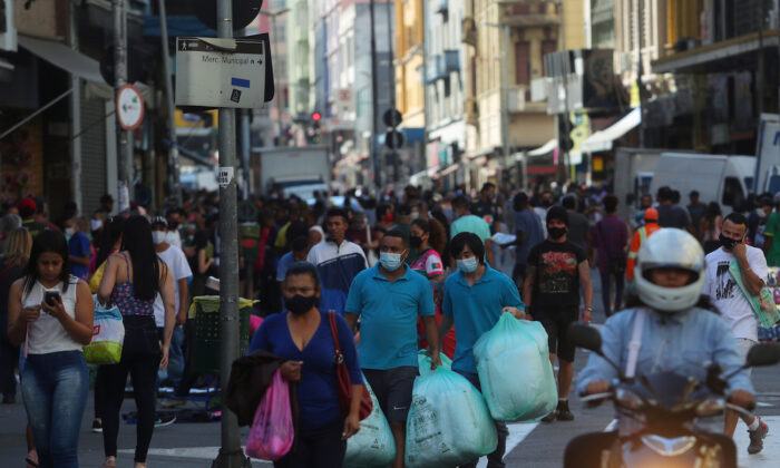 People walk with bags at a popular shopping street amid the CCP virus outbreak, in Sao Paulo, Brazil, June 19, 2020. (Amanda Perobelli/Reuters)