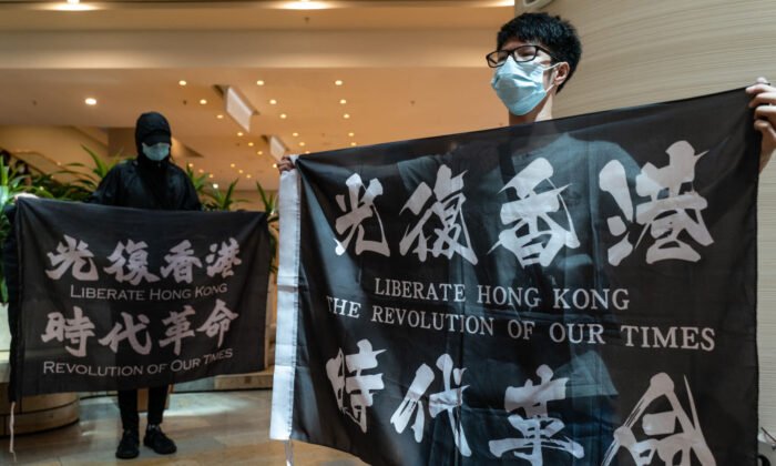 Pro-democracy supporters hold banners and shout slogans as they gather in a shopping mall during a lunch protest in Hong Kong on June 12, 2020. (Anthony Kwan/Getty Images)