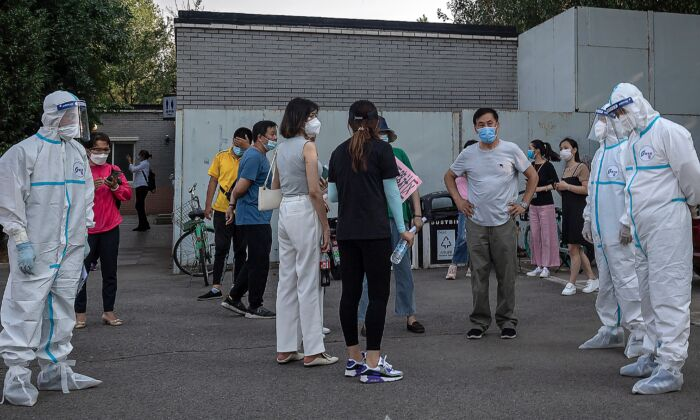 Workers wearing personal protective equipment take care of a group of people wearing face masks as they wait to undergo COVID-19 tests in Beijing on June 19, 2020. (NICOLAS ASFOURI/AFP via Getty Images)