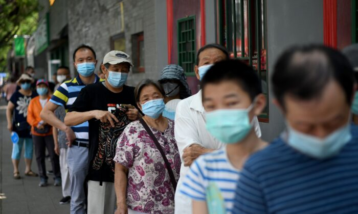 People line up to take a swab test during mass testing for the COVID-19 coronavirus in Beijing, China on June 21, 2020. (NOEL CELIS/AFP via Getty Images)