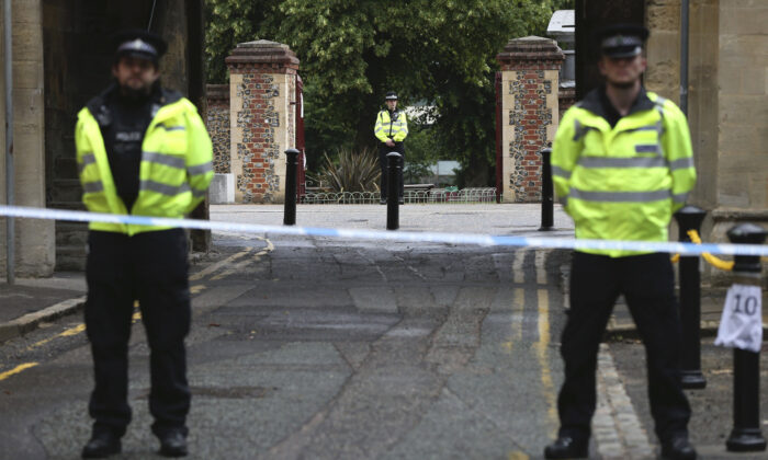 Police stand guard at the Abbey gateway of Forbury Gardens park in England's Reading town centre following a June 20 stabbing attack in the gardens, on June 21, 2020. (Jonathan Brady/PA via AP)