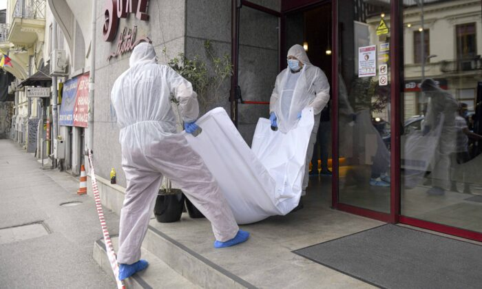Forensic workers carry the body of Gholamreza Mansouri from a hotel in downtown Bucharest, Romania, on June 19, 2020. (AP Photo/Andreea Alexandru)