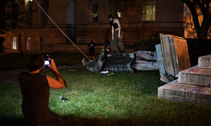 People stand around and take pictures with the statue of Confederate general Albert Pike after it was toppled by protesters at Judiciary square in Washington on late June 19, 2020. (ERIC BARADAT/AFP via Getty Images)