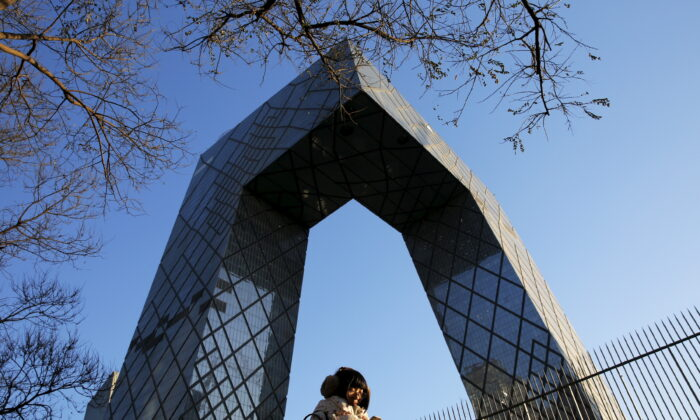 A morning commuter walks in front of the China Central Television (CCTV) building in Beijing on Dec. 2, 2015. (Damir Sagolj/Reuters)