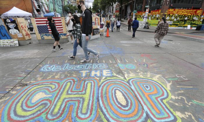 Pedestrians walk where streets are blocked off in what has been named the Capitol Hill Occupied Protest (CHOP) zone in Seattle, on June 21, 2020.  (Elaine Thompson/AP Photo)
