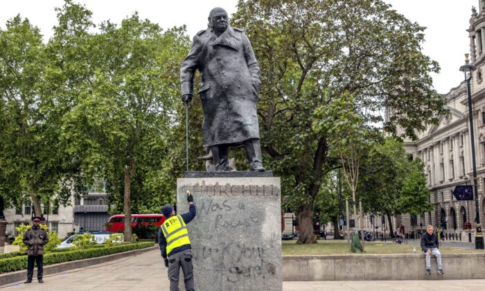 A worker cleans the statue of former prime minister Winston Churchill that was spray-painted with graffiti during a Black Lives Matter protest in Parliament Square, London, on June 8, 2020. (Dan Kitwood/Getty Images)