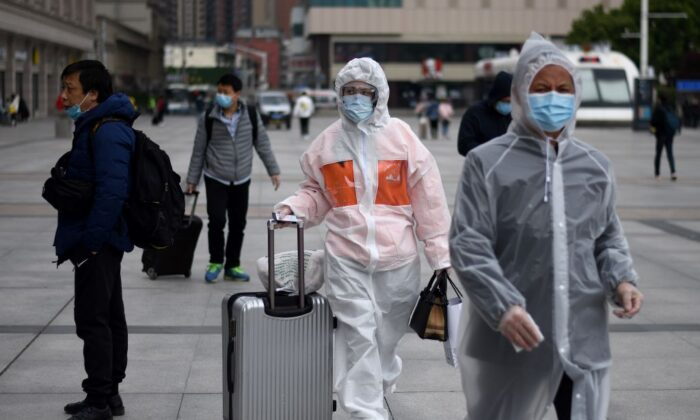 Passengers wearing face masks arrive at the Hankou railway station in Wuhan, China, on April 11, 2020. (Noel Celis/AFP via Getty Images)