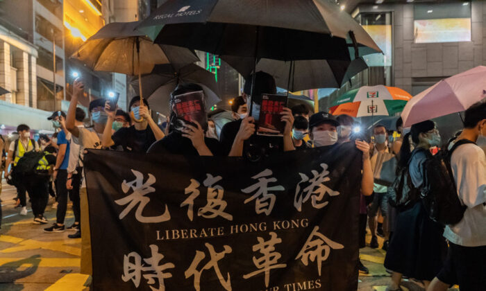 Protesters hold a banner as they march on a street during a rally in Central district in Hong Kong on June 9, 2020. (Anthony Kwan/Getty Images)