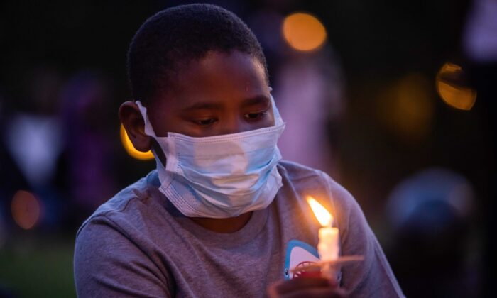 A boy holds a candle during a vigil around a makeshift memorial at the tree where Robert Fuller was found dead to demand a full investigation into Fuller's death, in Palmdale, Calif., on June 13, 2020. (Apu Gomes/AFP via Getty Images)