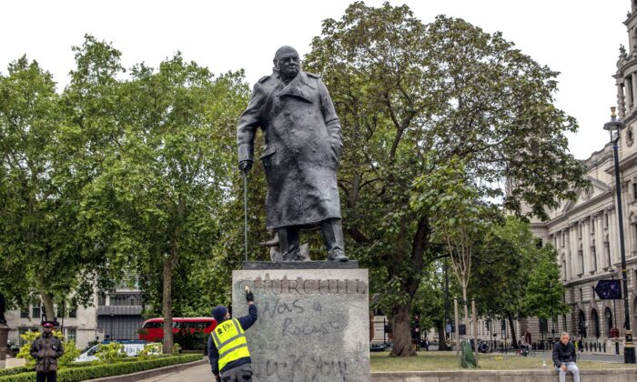 A worker cleans the statue of former prime minister Winston Churchill in London's Parliament Square that had been spray painted with graffiti during a Black Lives Matter protest on June 8, 2020. (Dan Kitwood/Getty Images)
