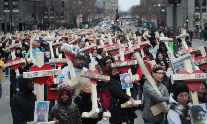 Residents, activists, and friends and family members of victims of gun violence march down Michigan Avenue carrying nearly 800 wooden crosses bearing the names of people murdered in the city in 2016 in Chicago on Dec. 31, 2016. (Scott Olson/Getty Images)