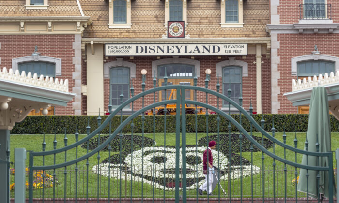 An employee cleans the grounds behind the closed gates of Disneyland Park on the first day of the closure, in Anaheim, Calif., on March 14, 2020. (David McNew/AFP via Getty Images)