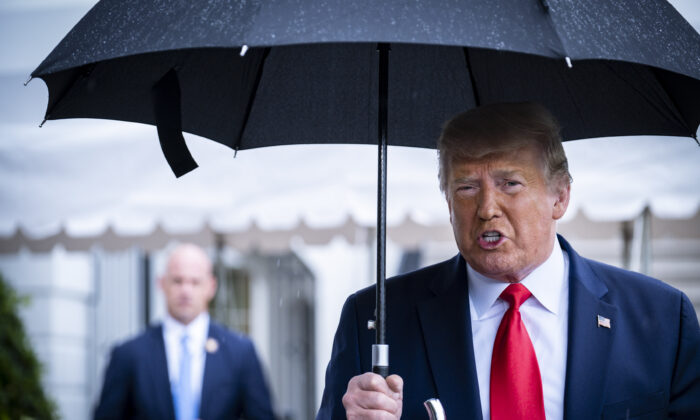 President Donald Trump stops to speak to the media in the rain on the South Lawn of the White House as he prepares to depart aboard Marine One for a rally in Tulsa, Okla., in Washington on June 20, 2020. (Pete Marovich/Getty Images)