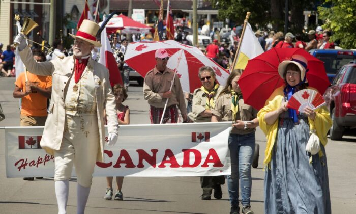 People take part in a Canada Day parade in Bobcaygeon, Ont., on July 1, 2019. (The Canadian Press/Fred Thornhill)
