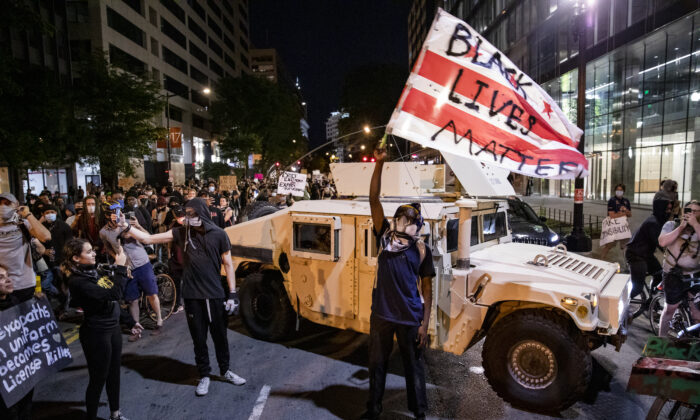 "A protester waves a DC flag with ""Black Lives Matter"" spray painted on it next to a DC National Guard Humvee during a demonstration over the death of George Floyd, who died in police custody, in Washington on June 2, 2020. (Samuel Corum/Getty Images)"