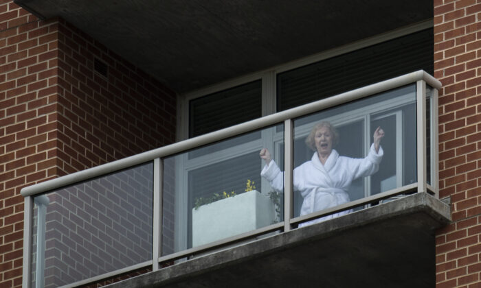 A resident of a senior living community dances on her balcony as she listens to a DC area motown band play a social distance concert in the community's parking lot in Arlington, Va., on April 14, 2020. (Andrew Caballero-Reynolds/AFP via Getty Images)