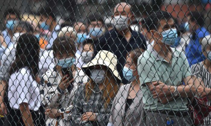 People gather at an outdoor area to take a swab test during mass testing for COVID-19 in Beijing on June 23, 2020. (NOEL CELIS/AFP via Getty Images)
