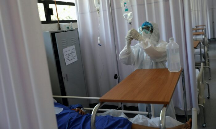 A medical staff is seen looking after a patient inside the provisional military hospital of the Campo Militar No. 1, which takes care of patients with symptoms of COVID-19 in Mexico City, Mexico, on June 9, 2020. (Carlos Jasso/Reuters)