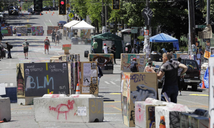 People walk amidst barricades in what has been named the Capitol Hill Occupied Protest zone in Seattle on June 22, 2020. (AP Photo/Ted S. Warren)