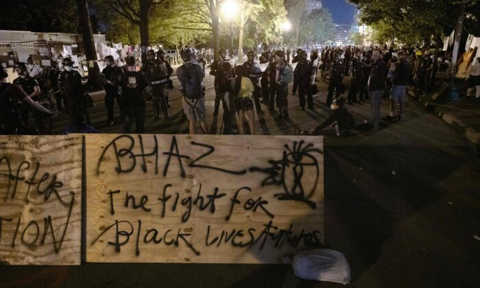 """Protesters confront police near a barricade they erected and marked with the sign """"Black House Autonomous Zone"""" in front of Lafayette Park near the White House in Washington on June 22, 2020. (Roberto Schmidt/AFP via Getty Images)"""