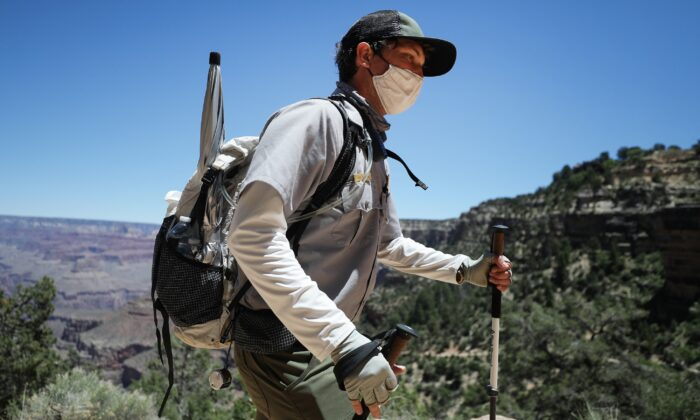 A park ranger wears a face mask while patrolling the Bright Angel trail in the South Rim of Grand Canyon National Park, which has partially reopened on weekends, in Grand Canyon National Park, Ariz., on May 25, 2020. (Mario Tama/Getty Images)