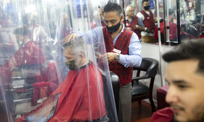 Peter Shamuelov (C) wears a protective mask as he gives a haircut to a customer at Ace of Cuts barbershop, in New York City, N.Y., on June 22, 2020. (John Minchillo/AP Photo)