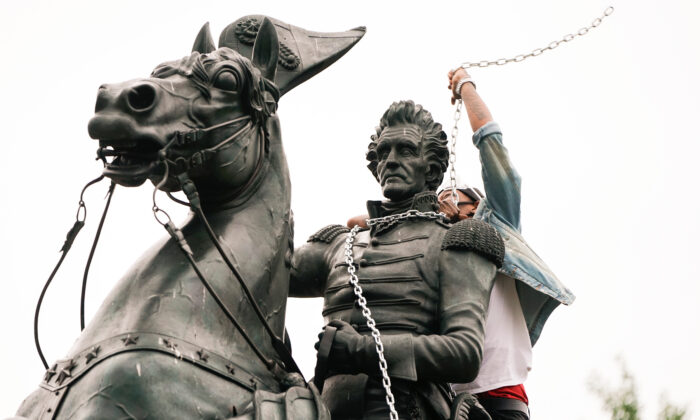 A vandal wraps chains around the neck of the statue of former President Andrew Jackson during an attempt by protesters to pull the statue down in the middle of Lafayette Park in front of the White House during racial inequality protests in Washington, on June 22, 2020. (Joshua Roberts/Reuters)