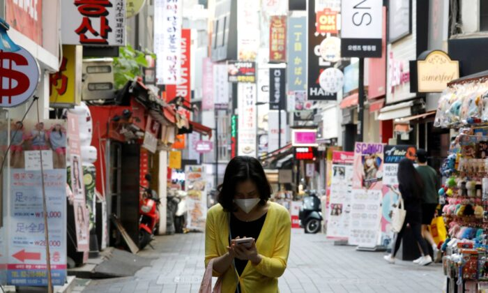 A woman wearing a mask looks at her mobile phone amid social distancing measures to avoid the spread of the novel coronavirus, in Myeongdong shopping district in Seoul, South Korea, May 28, 2020. (Kim Hong-Ji/Reuters)