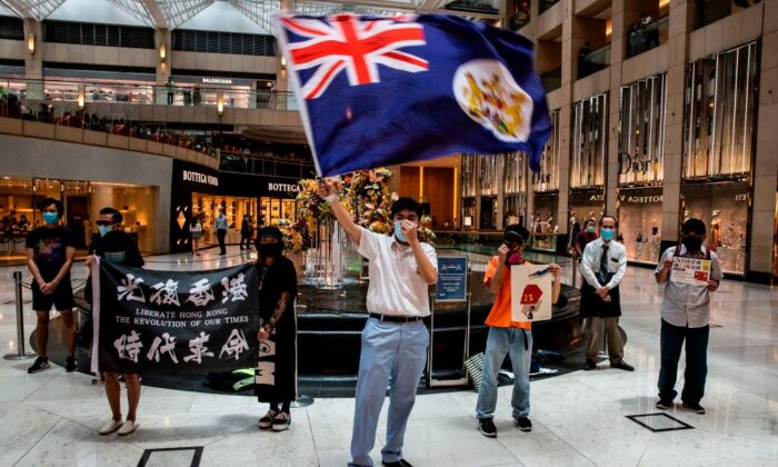 "A pro-democracy protester waves a British colonial flag during a ""Lunch With You"" rally at a shopping mall in the Central district in Hong Kong on June 1, 2020. (Issac Lawrence/AFP via Getty Images)"
