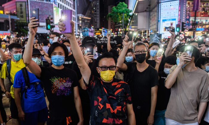 Pro-democracy activists hold up their mobile phone torches as they sing during a rally in the Causeway Bay district of Hong Kong on June 12, 2020. (Anthony Wallace/AFP via Getty Images)